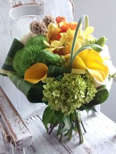 This bouquet was inspired by summer love. Soft tones of yellow, orange, green and brown were paired with strong structural flowers with hints of delicate blooms.