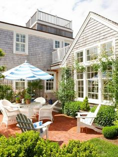 East coast patio area. White wicker furniture. Striped umbrella. boxwood hedges. Brick patio