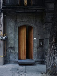 The facade of the house blends with the neighborhood, but the floating doorstep provides a clue to what lies beyond the threshold.