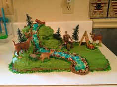 "Jerod's Deer Hunting Cake - 13x9 cake for bottom layer. Cut a 9"" round into pieces for top two layers. Graham crackers for the tent. Candles and pretzel sticks for the fire. River/waterfall was made by putting a layer of buttercream down first. Then piping gel on top. Used the ""Piping Gel Recipe that Works"" recipe. (easy for a beginner to follow and make) Rocks are chopped black walnuts. Not beautiful like the pros make, but my 4 year old son squeeled in delight. Priceless to me."