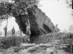 """MINISTRY INFORMATION FIRST WORLD WAR OFFICIAL COLLECTION (Q 2847)   A """"C"""" Battalion Tank mounting a parapet in a wood, near Elverdinghe, 11 September 1917."""