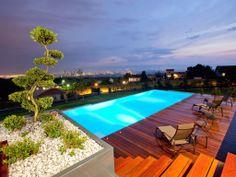 Le débordement par l'esprit piscine - 11,2 x 4,5 m Revêtement gris clair Margelles en pierre naturelle bleue Julie Plage en ipé