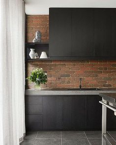 Black-stained: Kitchen cupboard joinery sits alongside exposed brick Photo: Shannon McGrath.