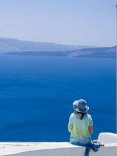 A Tourist Sits on a Stucco Wall Overlooking the Aegean Sea