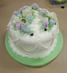 This is my very first cake covered in fondant.  I put too much icing underneath but other than that I think it turned out pretty well.  I just couldn't bring myself to do a pastel cake and leave it at that so I hid bugs among the flowers.  At work our QA department's job is to find bugs so I dedicated it to them.  The flowers are gumpaste, the bugs are royal icing.  It was my final cake for the Wilton Course III.