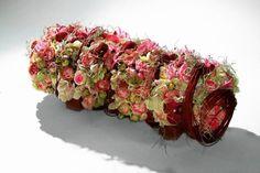 Dekoracje i stroiki na Wszystkich Świętych. Walec z gąbki florystycznej opleciony barwionymi wierzbowymi witkami, pomiędzy którymi umieszczono róże, falenopsisy, neriny, hortensje i pędy tilandsji