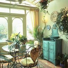 Rustic garden room, with green walls, wooden floor and indoor planting