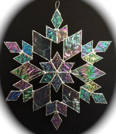 This stained glass snowflake was handcrafted in my home based studio using transparent, iridized glass with different textures. Measuring approximately 11 inches tip to tip, it comes ready to hang with an attached, soldered ring. The iridized textures of the glass make the snowflake