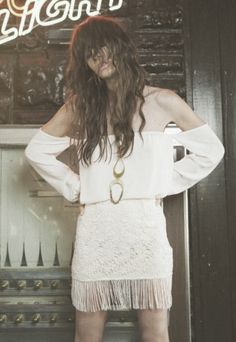 White off the shoulder dress with fringe.  Love the long wavy brown hair swaying in the wind.