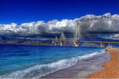Greece Gulf of Corinth cable-stayed bridge Rio Antirio water coast color stones pebbles sky clouds wallpaper background