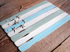 Weathered Paint Stick Beach Flag. (Could also use for Fourth of July with red and white paint stirrers and blue stars instead of starfish?)