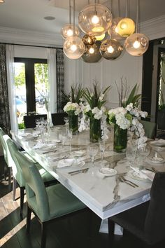this dining room with its gorgeous chandelier and marble table