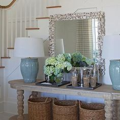 Chic cottage foyer features wainscoted staircase wall framing an oval console table filled with ... Urban Grace Interiors