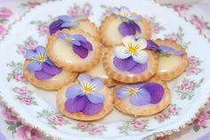 Mini sugar cream pies with edible pansy garnish.