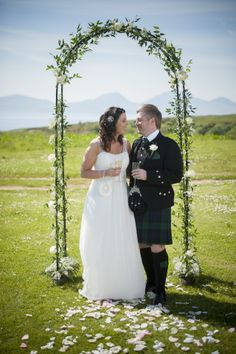 the happy couple under a beautiful floral archway with petals scattered along the asile