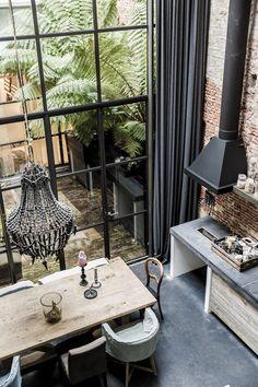Mélange de styles dans la cuisine : mur en brique, lustre, fauteuils et table en bois