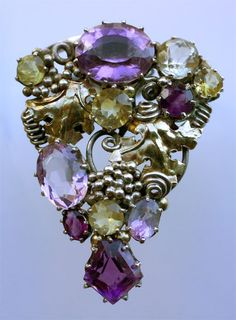 Dorrie Nossiter. Arts and Crafts clip brooch. Silver, gold, amethyst and citrine, c. 1930. H: 4.6 cm (1.81 in), W: 3.4 cm (1.34 in). Fitted case.