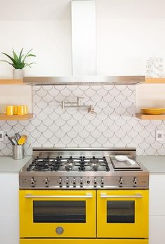 White and yellow kitchen features a stainless steel hood, flanked by stacked…