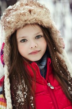 Cute little girl with beautiful green eyes and long brown hair standing in the snow