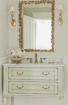 Light gray powder room with gold accents boast a light gray French washstand accented with gold pulls and a marble countertop with an antique brass faucet kit positioned beneath a gold leaves mirror flanked by gold sconces mounted on a light gray wall fin Powder Room Decor, Powder Room Design, Powder Rooms, Powder Room Lighting, French Country Cottage, French Country Decorating, Rustic French, Dream Bathrooms, Beautiful Bathrooms