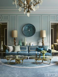 In the living room of a Paris apartment, which was designed by Jean-Louis Deniot, a sofa by Collection Pierre is upholstered in a Brochier fabric trimmed with ribbons by Samuel & Sons; lamps by Paul Evans flank a glass wall sculpture by Christophe Gaignon, the cocktail tables are custom designs, and the walls are painted in Paint Library's Eucalyptus. - ELLEDecor.com