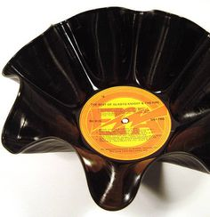Recycled Retro Record AlbumBowls - Make this in your oven!  Preheat your oven to 150 degrees F. Lay a large oven safe bowl upside down on a cookie sheet. Lay an old vinyl record album on the bowl, with the center directly above the bottom-center of the bowl. Heat for about five minutes - the record will begin to melt. Pull out the cookie sheet and start to mold the record to the bowl using oven mitts. Flipping the bowl up and molding it more will create the fluted design. Allow to cool.