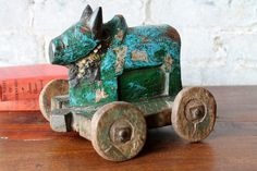 This is Nandi, the sacred Hindu cow pull-toy on wheels. This Nandi cow toy has brilliant original red color and time worn distressed finish.