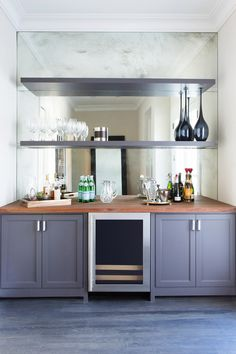 The bar area is backed with antiqued mirror, and the shelving and cabinets are painted in Iron Fixture by Dunn Edwards.