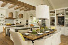 cuisine blanche spacieuse décorée de poutres apparentes, suspensions tressées et plans de travail en marbre gris