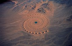 """""""Desert Breath"""" was a stunning and monumental land art installation located in the arid Sahara desert. Created by artist Danae Stratou, industrial designer Alexandra Stratou, and architect Stella Constantinides, this cosmic, swirling environmental artwork was constructed in 1997 over the span of two years. Centered on what had been a 98-foot artificial pool of water, 178 conical sand mounds and depressions spiral out to cover an area of nearly one million square feet."""