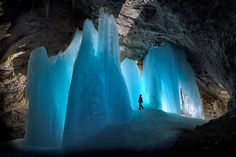 Picture of a caver next to ice formations in a cave in Austrian Alps