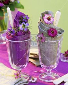 Place settings with purple flowers in water glasses.