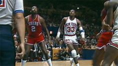 **GIF**  October 26, 1985 — Patrick Ewing makes his NBA debut in a game against the Philadelphia 76ers, rising above two of the league's all-time leading rebounders for the putback jam and the first points of his career.