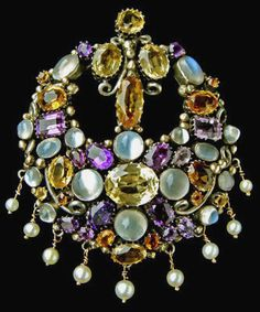 Dorrie Nossiter. Arts and Crafts clip brooch, c. 1930. Silver, gold, citrine, moonstone, amethyst and pearl.  Length: 7.8cm, width:5.8cm (3 x 2.3 in). Fitted case. Sold by Tadema Gallery.