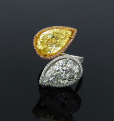 Fancy Yellow diamond ring, one pear-shaped Fancy Yellow VS2 diamond weighing 7.21 carats and one pear-shaped E SI1 diamond weighing 6.22 carats framed by Pink and White pave diamonds totaling 2.34 carats, hand-crafted in platinum and 18 karat pink gold