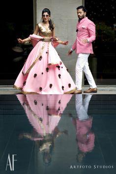 Candid Couple Shot- Bride in a Soft Pink And Bronze Lehenga with the Groom in a Pink and White Sherwani with White Pants | WedMeGood #wedmegood #indianbride #indianwedding #bridal #candidcoupleshot #lehenga #sangeetlehenga