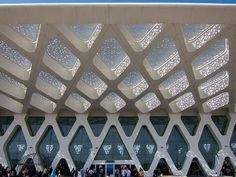 The white facade of Marrakech Menara Airport features intricate cutout patterns on the roof overhand that filter the sunlight beautifully. The arabesque patterns paired with the shape of the building blend modernism and traditional Islamic design flawlessly.
