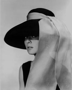 Black and white photo of Audrey Hepburn in a black dress and large floppy black hat with a white sash tied to the hat streaming down over her shoulders. Audrey Hepburn B Wall Art from Great Big Canvas. Audrey Hepburn Outfit, Audrey Hepburn Hut, Aubrey Hepburn, Audrey Hepburn Wallpaper, Audrey Hepburn Breakfast At Tiffanys, Hollywood Glamour, Old Hollywood, Hollywood Photo, George Peppard
