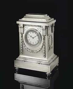 A SILVER MANTEL CLOCK MARKED K. FABERGÉ WITH THE IMPERIAL WARRANT, MOSCOW Of architectural form, the stepped rectangular base with ribbon-tied reeded border, case applied with chased laurel-leaf swags and ribbon-tied wreaths, centering a stiff-leaf bezel enclosing a white enamel dial, surmounted at each corner by fluted pilasters, with reeded stepped pediment, inscription in German, 'As a sign of sincere appreciation and for fond memories of Baron F. von Krauskopf Nov. 1907'.