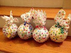 Party favor for ball themed birthday party. I found balls and the polka dotted tissue paper at dollar store. We wrapped the balls in the tissue paper and tied them up with primary colored ribbon. Will add on Thank You for BOUNCING In cards and the sign above the table will read Please take a party favor as you ROLL on out.