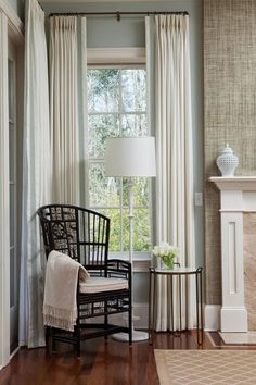 wallpaper on breast of fireplace, great idea. love the trim on curtains and rod, with cane armchair