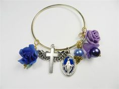 Handmade goldplated Christian theme bangle charm bracelet with 6 assorted charms   The bracelet fits approximatleya 7 1/2 wrist and is not adjustable   Two charms are pewter and there are 6 charms. They are as follows:Cross with wings, blue glass pearl, miraculous Virgin medal, resin lavender rose and blue rose and an acrylic tulip bead.   The charms move freely between the loops on the bracelet with the exception of the lavender rose which is stationary.   Please allow two days to make....