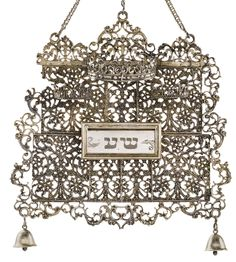 GERMAN SILVER TORAH SHIELD  of cartouche form in cast filigree sections, the sides with Renaissance caryatid brackets, mounted above the compartment with three crowns, hung with two bells, fitted with one reversible portion plaque, the chains with cartouche-form hook. marked on top of shield and hook. Circa 1700 Johann Valentin Schüller, Frankfurt am Main