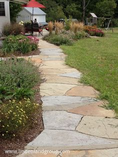 A casual bluestone flagging pathway connects the driveway to the back yard