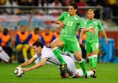 Karim Matmour Photos - Gareth Barry of England is tackled by Karim Matmour of Algeria during the 2010 FIFA World Cup South Africa Group C match between England and Algeria at Green Point Stadium on June 18, 2010 in Cape Town, South Africa. - England v Algeria: Group C - 2010 FIFA World Cup