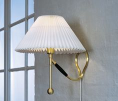 Pair of Danish Kaare Klint LeKlint 306 brass/paper handpleated shades.  One of the first LeKlint designs, swivels from table lamps to wall pin-ups.