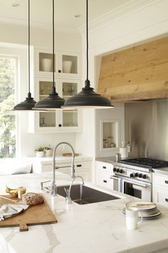 white kitchen cabinets glass fronts, stained range hood,black hanging lights