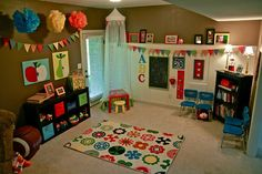 Love the bunting and chalkboard. Fun rug for a play room too :).