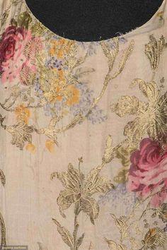TWO CHIFFON PRINT GOWNS, EARLY 1930s. 1 w/ lilac & rose print & metallic gold lame, sleeveless, drop waist, double layer skirt w/ irregular hems, pink taffeta side sash. 1 ivory chiffon, w/ peony blossom printin pink, lilac & yellow, pink chiffon hem frills, shaped elbow length sleeves. Detail