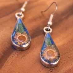 Fair Trade Nahua Dried Flower Earrings — handmade in Mexico — find it at http://fairandsquareimports.com/jewelry/nahua-dried-flower-earrings-mexico — These teardrop-shaped earrings are handmade with alpaca silver. They encase actual yellow flowers in a clear resin. Hypoallergenic hooks.